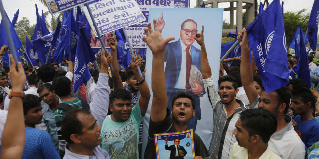 Dalits hold portraits of prominent freedom fighter Bhim Rao Ambedkar and protest against the alleged attack on community members for skinning a cow in Una, in Ahmadabad, India, Tuesday, July 19, 2016. (AP Photo/Ajit Solanki)