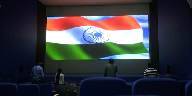 This picture taken on March 17, 2017 shows audience members standing for the Indian national anthem before a movie starts at the Regal cinema, an 84-year-old movie hall, in the heart of the Indian capital New Delhi.
