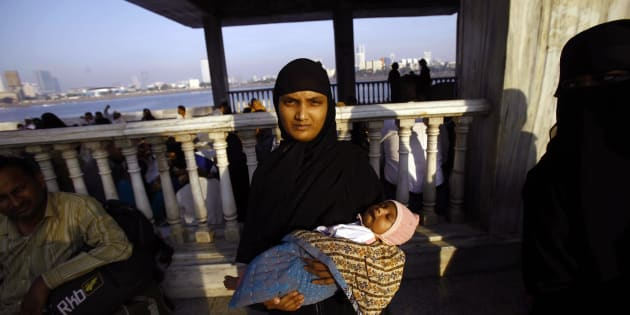 A Muslim woman holds her child and stands at the Haji Ali Dargah in Mumbai, India, Thursday, Nov. 8, 2012.