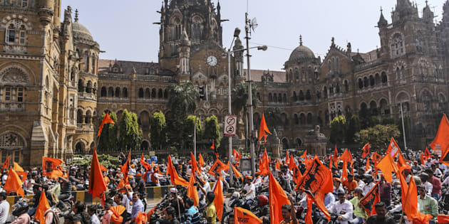 Demonstrators with saffron flags ride motorcycles past the Chhatrapati Shivaji Terminus railway station during a silent protest organized by Marathas in Mumbai on 6 November 2016. Photographer: Dhiraj Singh/Bloomberg via Getty Images