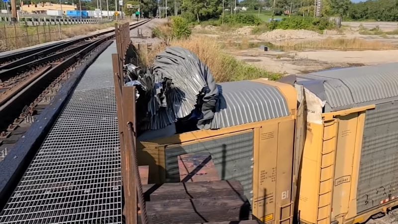 Watch a train car damage a load of new cars under a low bridge