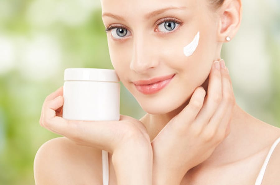 cute woman applying cream to...