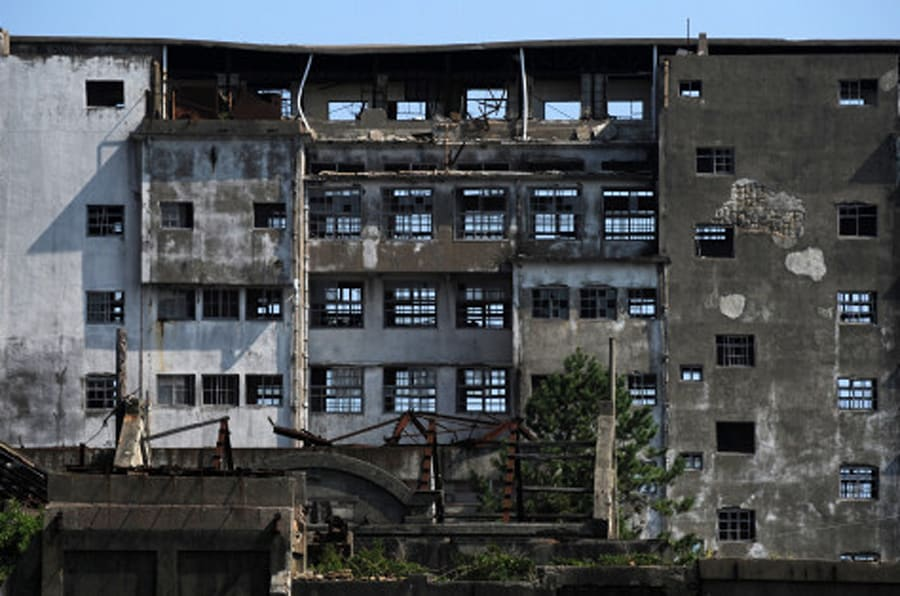 NAGASAKI, JAPAN - SEPTEMBER 23:  Hashima Island, as known as 'Battleship island (Gunkan-jima)' is seen on September 23, 2013 in Nagasaki, Japan. The island was a coal mining facility until its closure in 1974, more than 5,000 residents used to live this Japan's first concrete buidling apartments at its peak, there used to be a hospital, schools or even a theatre.  (Photo by Masashi Hara/Getty Images)