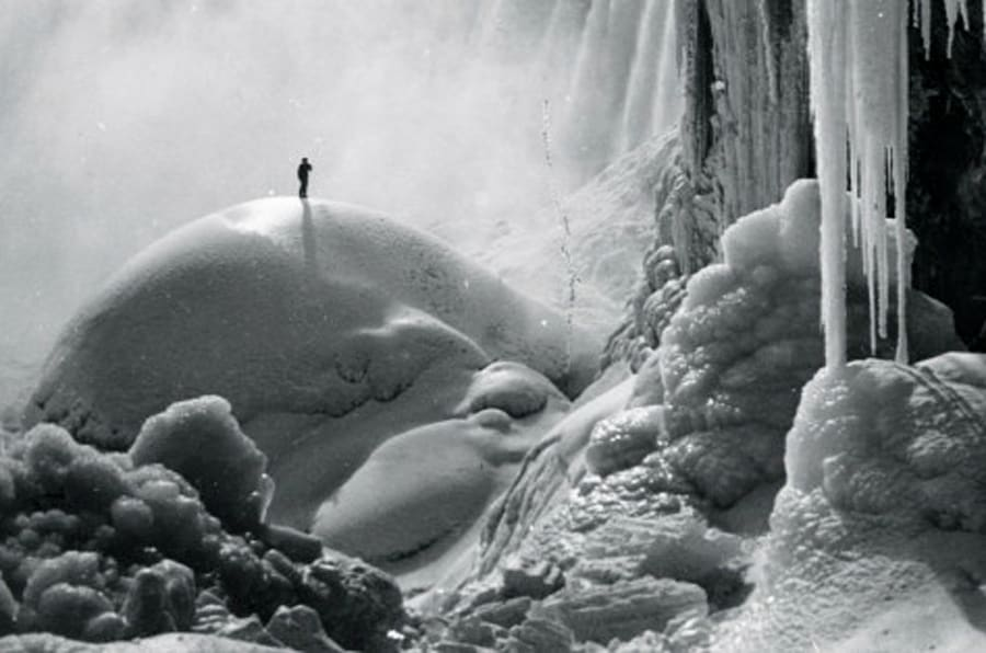 UNSPECIFIED - CIRCA 1903:  Sole Adventurer stand on an ice dome beneath the icicled Niagara Falls in a Frozen Wonderland  (Photo by Buyenlarge/Getty Images)