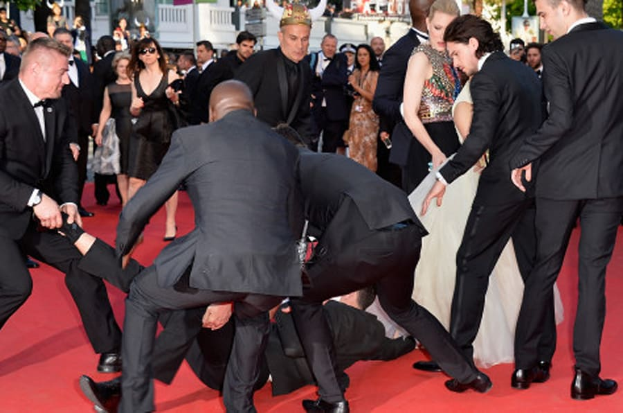 CANNES, FRANCE - MAY 16:  A man invades the Red Carpet and is held by security at the 'How To Train Your Dragon 2' premiere during the 67th Annual Cannes Film Festival on May 16, 2014 in Cannes, France.  (Photo by Pascal Le Segretain/WireImage)