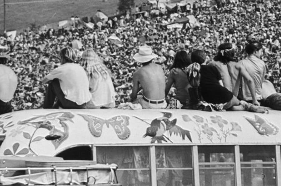 Fans sitting on top of a painted bus at the Woodstock Music Festival, Bethel, New York, 15th-17th August 1969. (Photo by Hulton Archive/Getty Images)