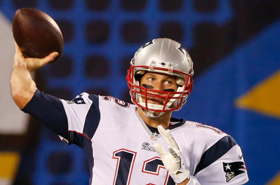 New England Patriots quarterback Tom Brady throws during warm ups before facing the San Diego Chargers in an NFL football game Sunday, Dec. 7, 2014, in San Diego. (AP Photo/Lenny Ignelzi)