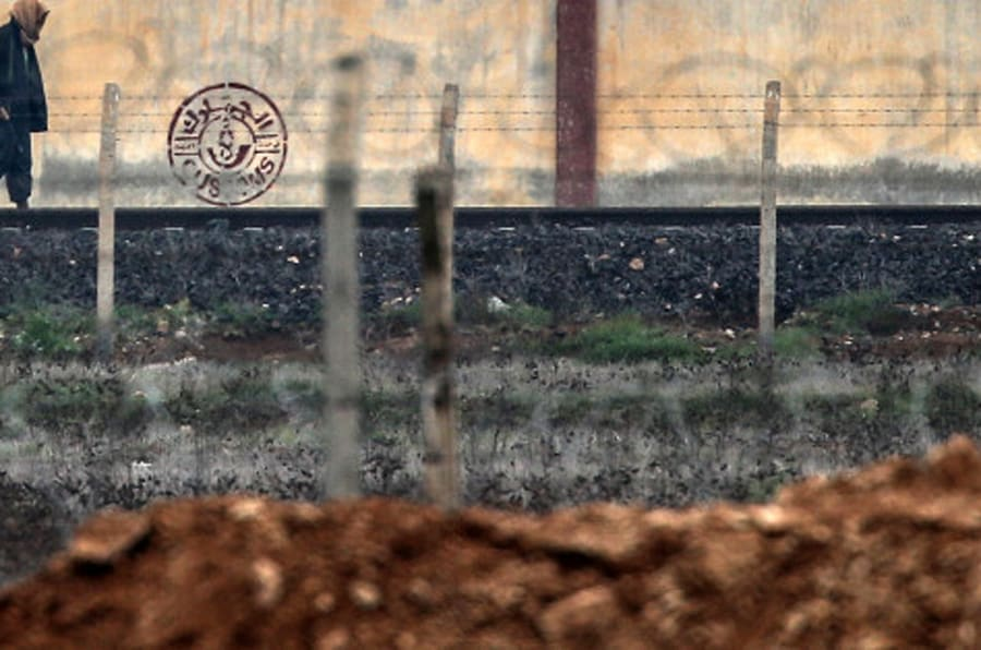 An armed man walks in IS-controlled Tal Abyad across the Turkish Akcakale border gate, Turkey, Saturday, Jan. 31, 2015 as some people wait for the possible release of Japanese journalist Kenji Goto, kidnapped by the Islamist militant group in Syria. The fate of a Japanese journalist and Jordanian military pilot were unknown Friday, a day after the latest purported deadline for a possible prisoner swap passed with no further word from the Islamic State group holding them captive.(AP Photo/Emrah Gurel)