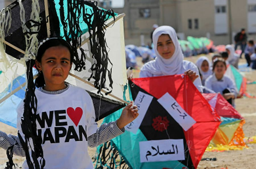 Palestinian students prepare to fly their kites during a commemoration to mark the fourth anniversary of Japan's Tsunami organized by the United Nations Relief and Works Agency, in Khan Younis, southern Gaza Strip, Monday, March 9, 2015. (AP Photo/Adel Hana)
