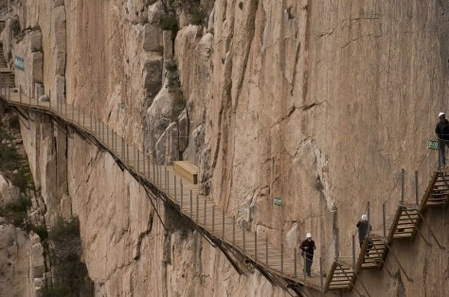 Journalists walk during a visit to the foot-path 'El Caminito del Rey' (King's little path) a narrow walkway hanging and carved on the steep walls of a defile in Ardales near Malaga on March 15, 2015. The one meter wide and 7.7 km long path, hanging from Ardales' defile at 100 meter high, was closed in the mid 90's after several hikers resulted dead when walking it. Once restored it will be reopened to the public on March 28, 2015.   AFP PHOTO/ JORGE GUERRERO        (Photo credit should read Jorge Guerrero/AFP/Getty Images)