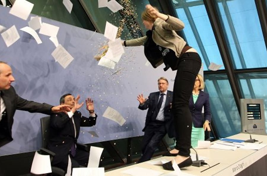 A woman interrupts a press conference by Mario Draghi (C), President of the European Central Bank, (ECB) following a meeting of the Governing Council in Frankfurt / Main, Germany, on April 15, 2015. AFP PHOTO / DANIEL ROLAND        (Photo credit should read DANIEL ROLAND/AFP/Getty Images)