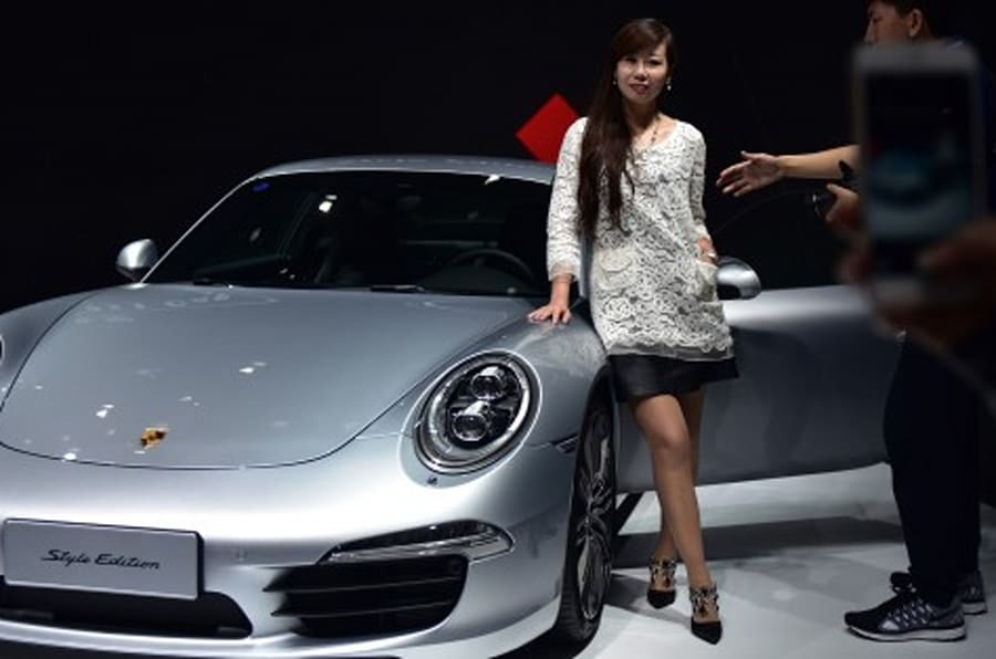 A woman poses next to a Porsche 911 Carrera Style Edition at the 16th Shanghai International Automobile Industry Exhibition in Shanghai on April 20, 2015. Global car makers showed off hundreds of vehicles in China's commercial hub Shanghai on April 20, as the world's biggest auto market continues to attract despite a sharp deceleration in sales growth. AFP PHOTO / JOHANNES EISELE        (Photo credit should read JOHANNES EISELE/AFP/Getty Images)
