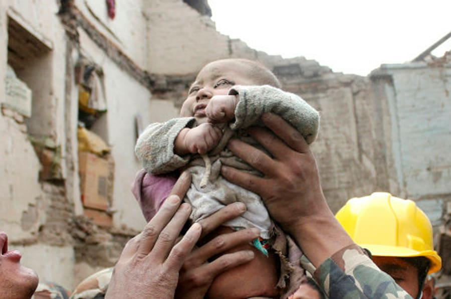 "In this Sunday, April 26, 2015, photo taken by Amul Thapa and provided by KathmanduToday.com, four-month-old baby boy Sonit Awal is held up by Nepalese Army soldiers after being rescued from the rubble of his house in Bhaktapur, Nepal, after Saturday's 7.8-magnitude earthquake shook the densely populated Kathmandu valley.  Thapa says that when he saw the baby alive after 20 hours of rescue efforts all my sorrow went. Everyone was clapping. It gave me energy and made me smile in spite of lots of pain hidden inside me."" (Amul Thapa/KathmanduToday.com via AP)"