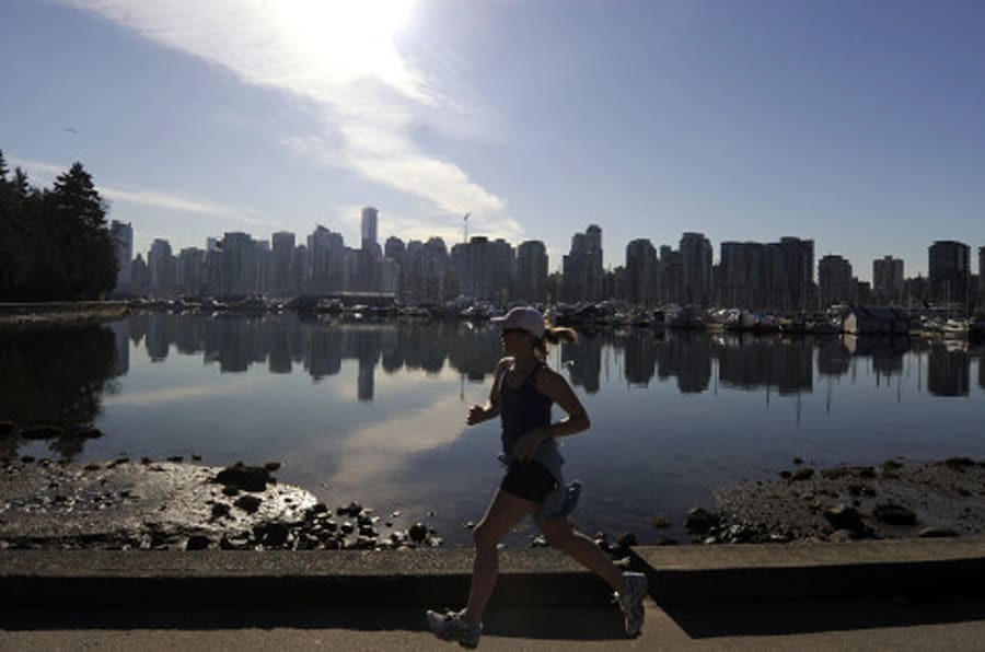 A woman joggs in Stanley Park in front of the Vancouver Skyline on February 19, 2010, during the Vancouver Winter Olympics.   AFP PHOTO DDP / DAVID HECKER (Photo credit should read DAVID HECKER/AFP/Getty Images)