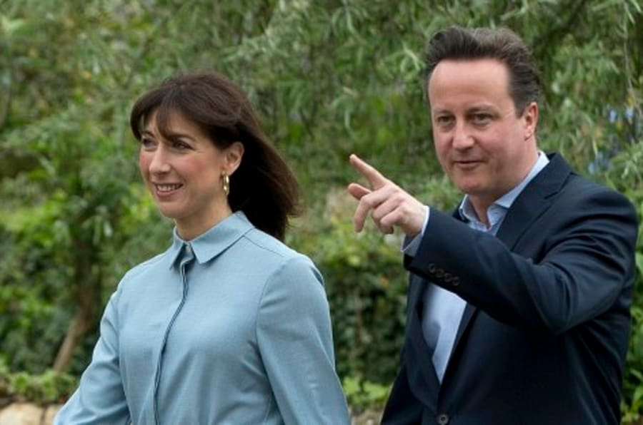 Britain's Prime Minister and Conservative Party leader David Cameron and his wife Samantha arrive to vote at a polling station in Spelsbury, England, as they vote in the general election, Thursday, May 7, 2015.   Polls have opened in Britain's national election, a contest that is expected to produce an ambiguous result, a period of frantic political horse-trading and a bout of national soul-searching.  (AP Photo/Alastair Grant)