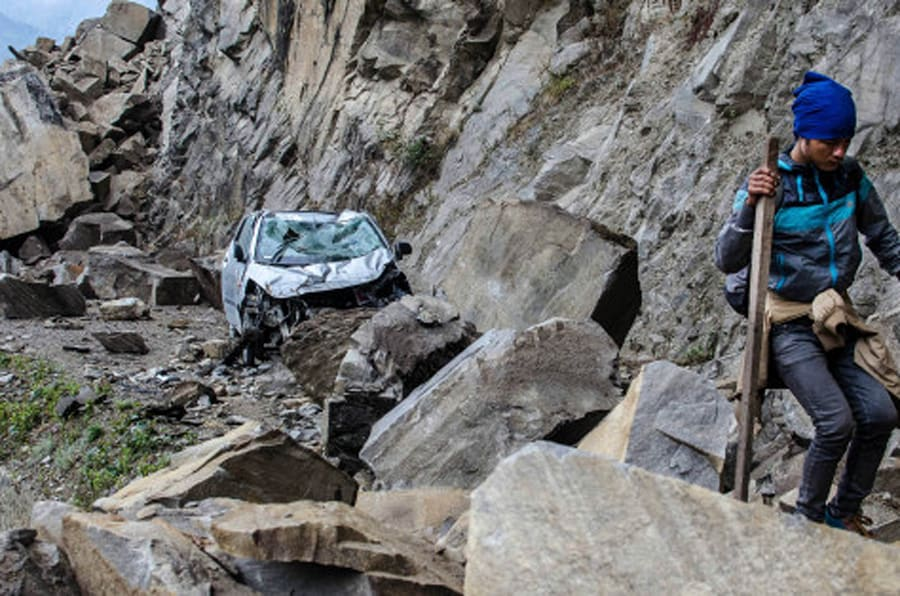 In this Monday, April 27, 2015 photo, a Nepalese man walks over fallen rocks and past a crushed car on the way to Dhunche, Nepal, a village in Langtang National Park, two days after a 7.8-magnatude earthquake hit the region. The photographer, Joe Sieder, said the man was part of a group of Nepalese workers and trekkers who left Syabrubesi earlier that day and hiked about 30 km (19 miles) for 13 hours, mostly over boulder-strewn roads with some small landslides along the way to make their way to a passable road. (Joe Sieder via AP)  MANDATORY CREDIT