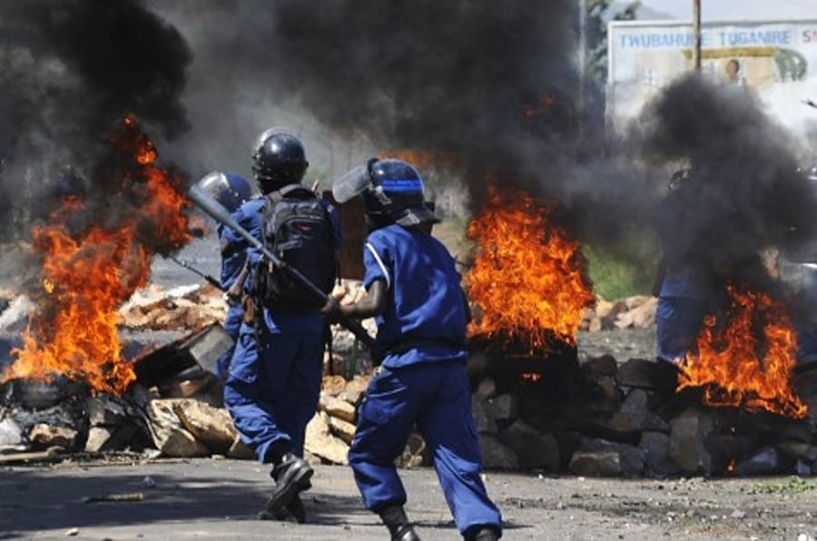 Burundian riot police run past a tire fire during a protest against the president's bid to cling to power for a third term in Musaga, ourskirts of Bujumbura, on April 28, 2015. At least five people have died since clashes broke out on April 26 after the ruling CNDD-FDD party, which has been accused of intimidating opponents, designated President Pierre Nkurunziza its candidate in the June 26 presidential election.  On April 28, a spokesman for the President Nkurunziza said the President 'won't back down.' AFP PHOTO / SIMON MAINA        (Photo credit should read SIMON MAINA/AFP/Getty Images)