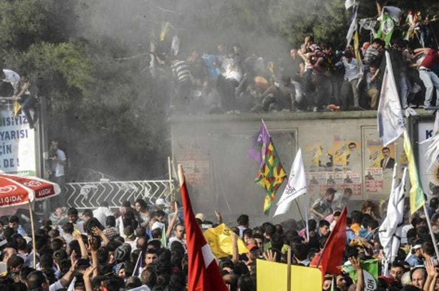 People look at smoke from an explosion which injured several people during a rally by the pro-Kurdish People's Democratic Party (HDP) on June 5, 2015 in Diyarbakir, two days ahead of legislative polls. The HDP has been targeted by several attacks ahead of June 7 elections and clashes at its rally in the eastern city of Erzurum on june 6 left dozens wounded. AFP PHOTO / ILYAS AKENGIN        (Photo credit should read ILYAS AKENGIN/AFP/Getty Images)