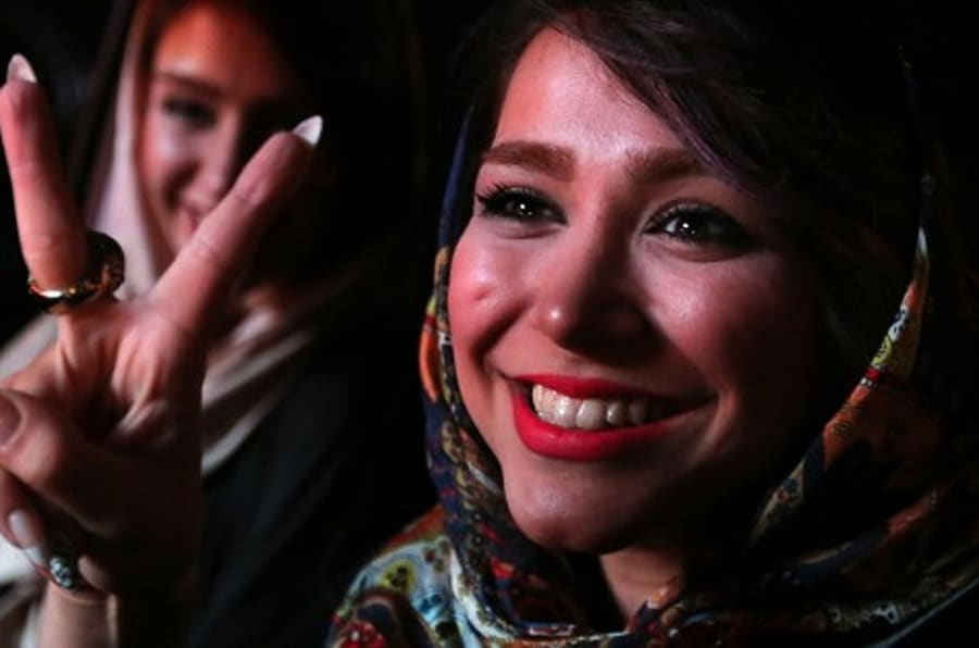 Iranian women flash the v sign for victory during celebration in northern Tehran on July 14, 2015, after Iran's nuclear negotiating team struck a deal with world powers in Vienna. Iranians poured onto the streets of Tehran after the Ramadan fast ended at sundown Tuesday to celebrate the historic nuclear deal agreed earlier with world powers in Vienna. AFP PHOTO/ATTA KENARE        (Photo credit should read ATTA KENARE/AFP/Getty Images)