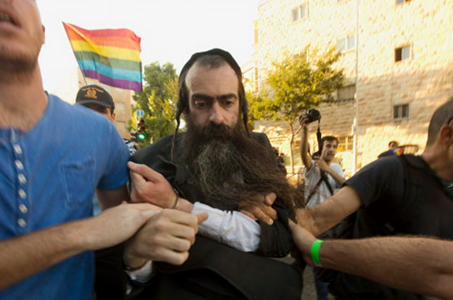 Ultra Orthodox Jew Yishai Schlissel is detained by plain-clothes police officers after he stabbed people during a gay pride parade in Jerusalem on Thursday, July 30, 2015. Schlisse was recently released from prison after serving a term for stabbing several people at a gay pride parade in 2005, a police spokeswoman said. (AP Photo/Sebastian Scheiner)