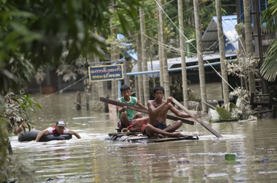 Flood-affected residents use make-shift rafts to travel through floodwaters in Kalay, upper Myanmar's Sagaing region on August 3, 2015. Relentless monsoon rains have triggered flash floods and landslides, destroying thousands of houses, farmland, bridges and roads -- with fast-flowing waters hampering relief efforts.  AFP PHOTO / Ye Aung THU        (Photo credit should read Ye Aung Thu/AFP/Getty Images)