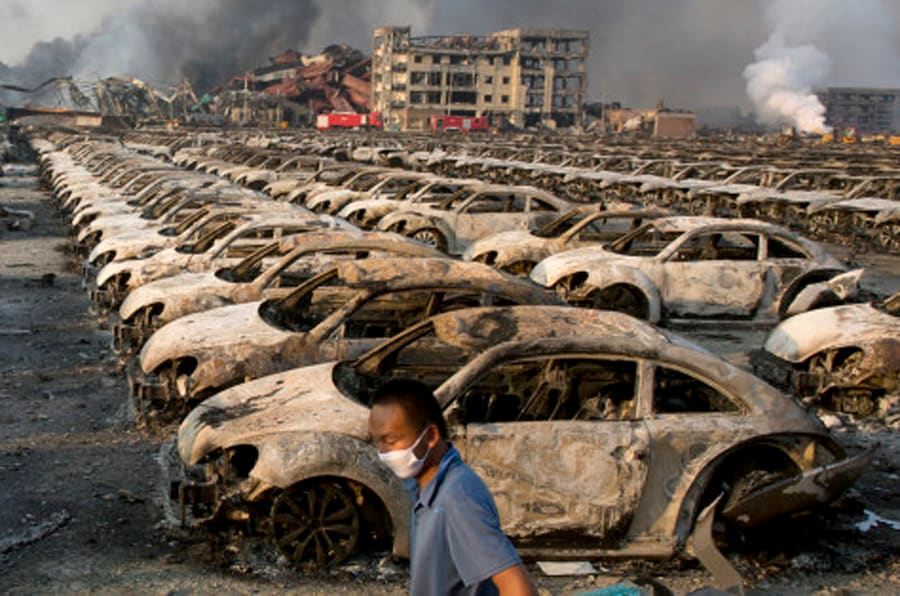 In this photo taken Thursday, Aug. 13, 2015, a man walks past the charred remains of new cars at a parking lot near the site of an explosion at a warehouse in northeastern China's Tianjin municipality. Rescuers have pulled a survivor from an industrial zone about 32 hours after it was devastated by huge blasts in China's Tianjin port. Meanwhile, authorities are moving gingerly forward in dealing with a fire still smoldering amid potentially dangerous chemicals. (AP Photo/Ng Han Guan)