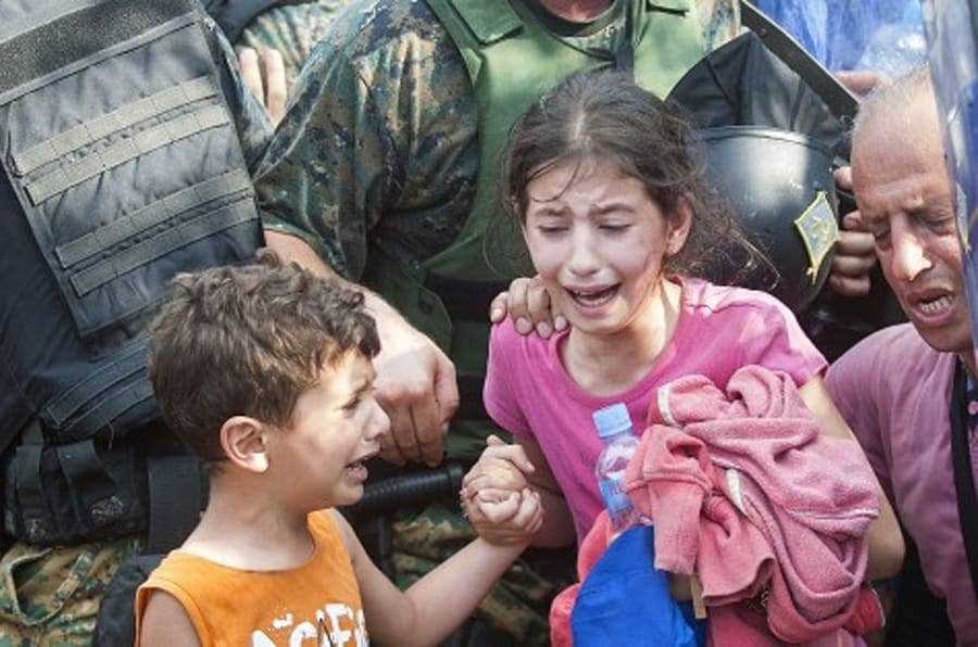 A young girl and boy cry as police block a group of migrants trying to cross the Macedonian-Greek border near the town of Gevgelija on August 21, 2015. Macedonia said on August 20 that it had declared a 'state of emergency' on its southern border with Greece and would draft in the army to help control the influx of migrants crossing the frontier. AFP  PHOTO / ROBERT ATANASOVSKI        (Photo credit should read ROBERT ATANASOVSKI/AFP/Getty Images)
