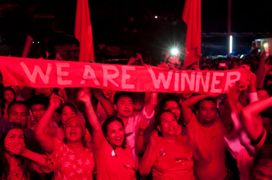 Supporters of Myanmar opposition leader Aung San Suu Kyi's National League for Democracy party holding a banner cheer as they watch the result of general election on an LED screen outside the party's headquarters Sunday, Nov. 8, 2015, in Yangon, Myanmar. Myanmar voted Sunday in historic elections that will test whether popular mandate can loosen the military's longstanding grip on power, even if opposition leader Aung San Suu Kyi's party secures a widely-expected victory. (AP Photo/Khin Maung Win)