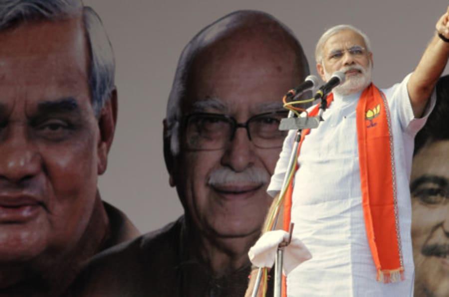 Gujarat state Chief Minister Narendra Modi addresses a rally in Ahmadabad, India, Sunday, Sept. 25, 2011.Portraits of senior Bharatiya Janata Party (BJP) leaders Atal Bihari Vajpayee, left , Lal Krishna Advani, center and party president Nitin Gadkari are seen behind. (AP Photo/Ajit Solanki)