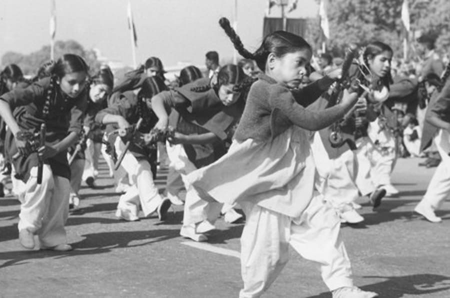 A group of young girls playing instruments and dancing during a march past to celebrate India's 11th Republic Day in Delhi.