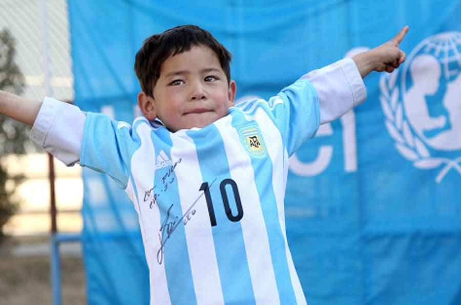 In this provided by UNICEF, Murtaza Ahmadi, an Afghan Lionel Messi fan, shows a donated and signed shirt by Messi, in Kabul, Afghanistan, Thursday, Feb. 25, 2016. (Mahdy Mehraeen/UNICEF via AP)