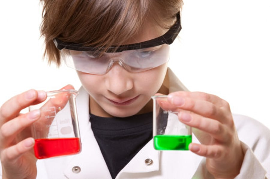 A close up of a 12 year old boy holding tow beakers of liquid as he compares them.