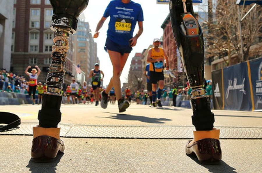 BOSTON - APRIL 18: Boston Marathon bombing survivor Celeste Corcoran stands on the finish line as she waits for runners in her running group, 50 Legs, to cross the finish line of the 120th Boston Marathon on Monday, April 18, 2016. Celeste lost both legs in the 2013 marathon bombing. Officials let her stand there to watch the runners. (Photo by John Tlumacki/The Boston Globe via Getty Images)