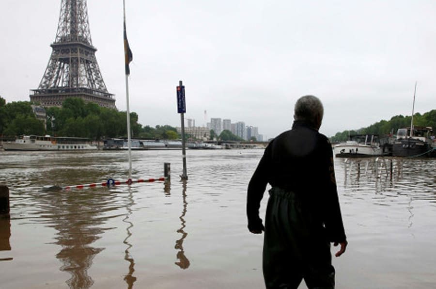 A man walks on a flooded road near his houseboat moored near the Eiffel towel during flooding on the banks of the Seine River in Paris, France, after days of almost non-stop rain caused flooding in the country June 2, 2016. REUTERS/Pascal Rossignol     TPX IMAGES OF THE DAY