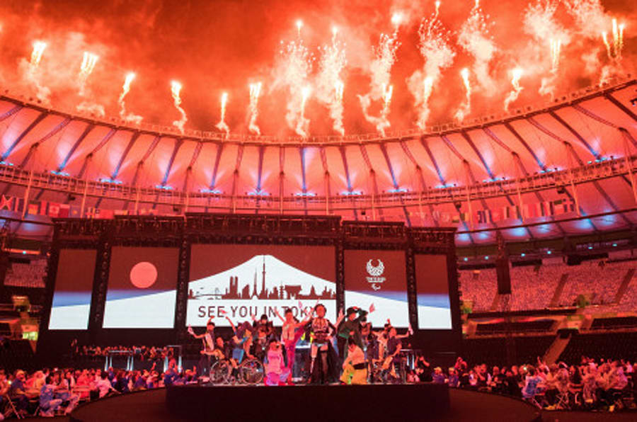 """In this photo released by the IOC, a sign saying """"see you in Tokyo"""" appears behind Koichi Omae and four female dancers are joined on stage by GIMICO, Aya Sato and Bambi walking triumphantly down the runway gathering around Akira Hiyama during the closing ceremony of the Rio 2016 Paralympic Games at the Maracan' Stadium in Rio de Janeiro, Brazil , Sunday, Sept. 18, 2016. (Thomas Lovelock/OIS, IOC via AP)"""