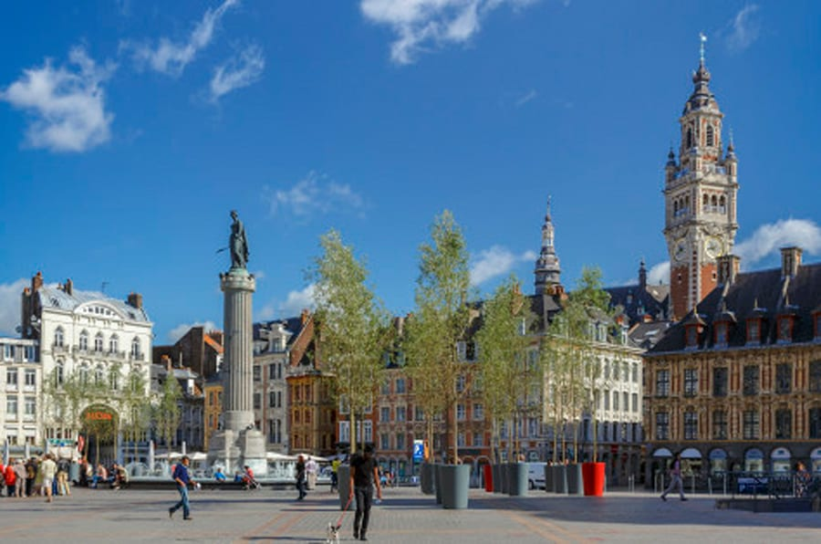 Grand Place with the Belfry tower of the Chamber of Commerce and the statue of  the Column of the Goddess (memorial of the siege of 1792).