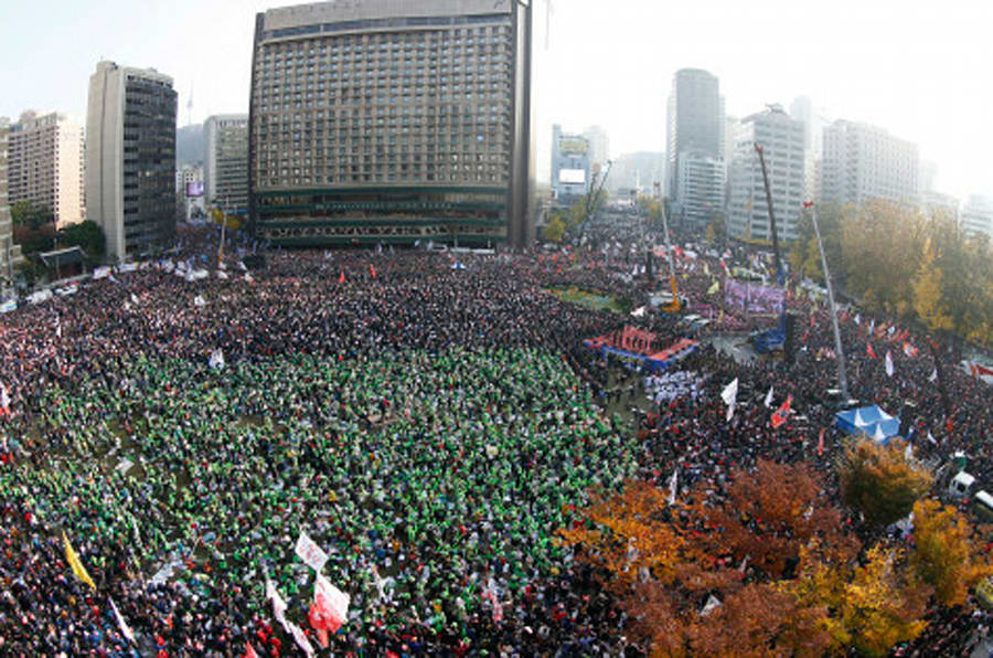 In this photo made with a fish-eye lens, South Korean people shout slogans during a protest against South Korean President Park Geun-hye on a main street in Seoul, South Korea Saturday, Nov. 12, 2016. Tens, and possibly hundreds, of thousands of South Koreans were expected to rally in Seoul on Saturday demanding the ouster of President Park in what would be one of the biggest protests in the country since its democratization about 30 years ago. (Jeon Heon-kyun/Pool Photo via AP)