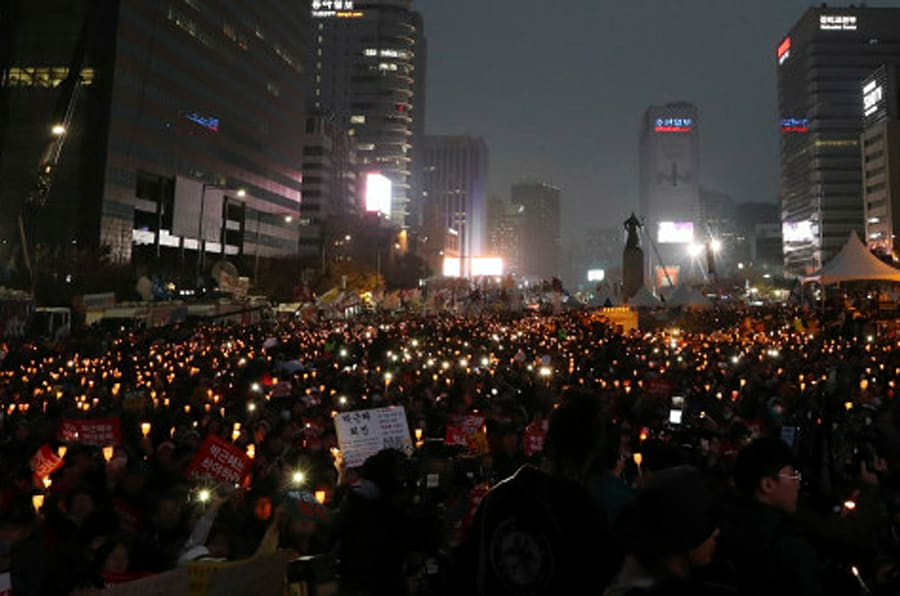 South Korean protesters hold up candles during a rally calling for South Korean President Park Geun-hye to step down in Seoul, South Korea, Saturday, Nov. 19, 2016. For the fourth straight weekend, masses of South Koreans were expected to descend on major avenues in downtown Seoul demanding an end to the presidency of Park, who prosecutors plan to question soon over an explosive political scandal. (AP Photo/Lee Jin-man)