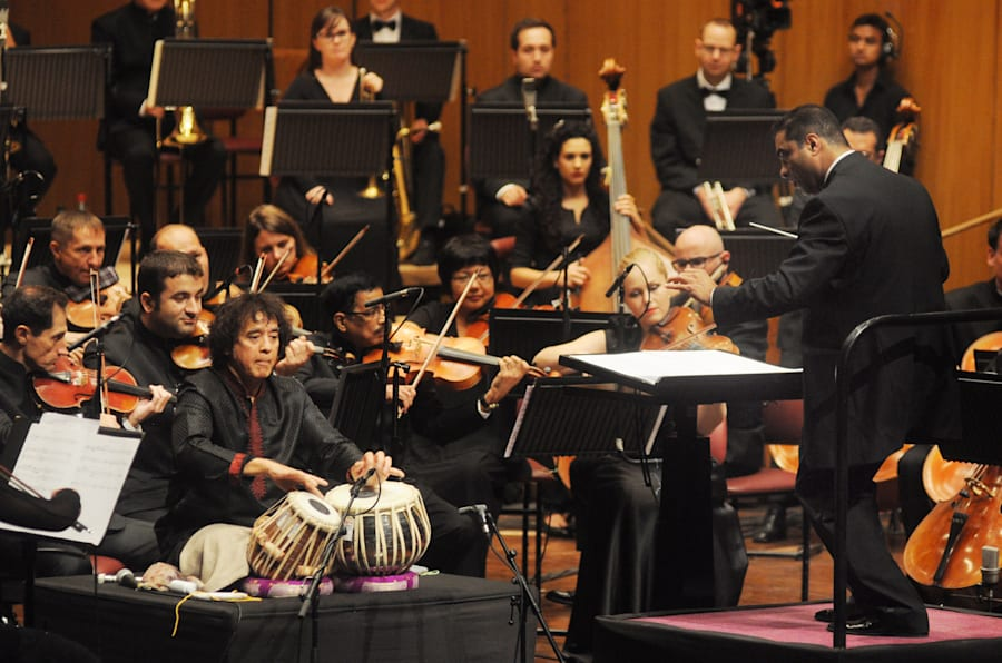 Associate Music Director Zane Dalal leads the world premiere performance Zakir Hussain's 'Peshkar', with Hussain as the soloist. 'Peshkar', a concerto for tabla and orchestra, was the first piece commissioned by the SOI.