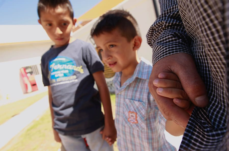 El migrante salvadoreño Epigmenio Centeno y sus hijos, Axel Jaret (de 9 años) Steven Atonay (3 años), posan para una foto afuera del albergue Casa del Migrante, en México, donde Epigmenio decidió quedarse por la política de separación de familias de Donald Trump.