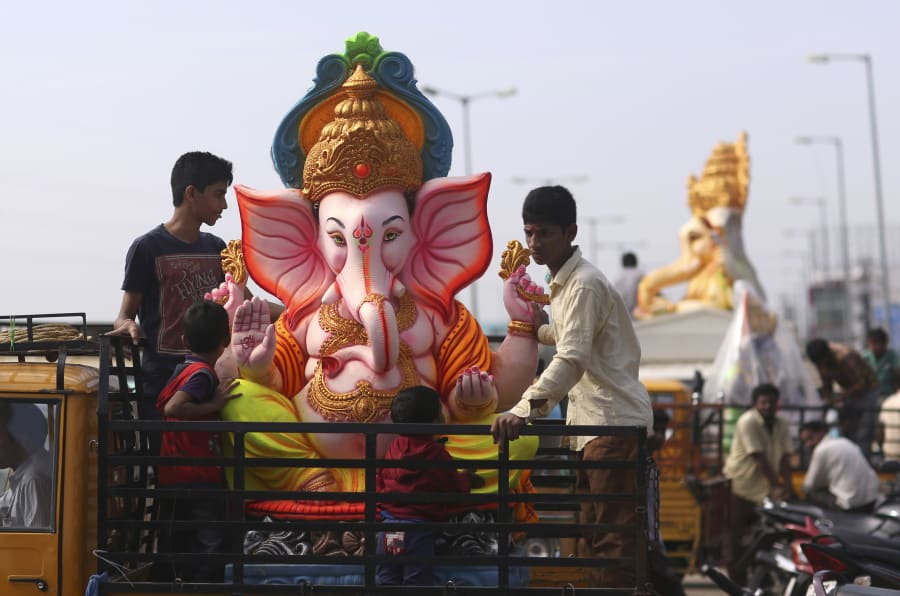 Devotees carry an idol of elephant-headed Hindu god Ganesha to worship it on occasion of Ganesh Chaturthi festival, in Hyderabad, India, Monday, Sept. 5, 2016. The idol will be immersed in water bodies after worship at the end of the festival. (AP Photo/Mahesh Kumar A.)