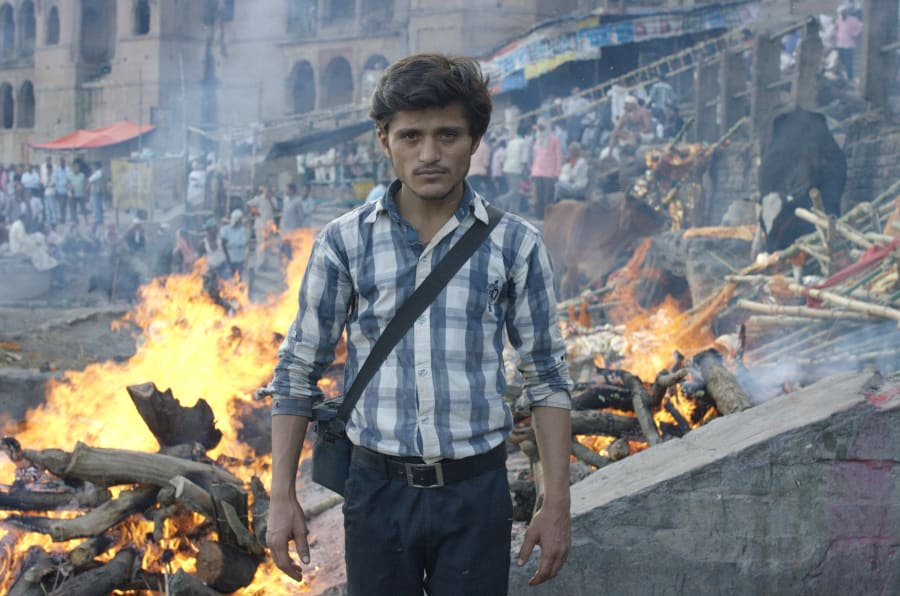 'Nadi the death photographer' stands afront the burning ghats of Varanasi, India.
