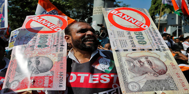 A man holds placards and shouts slogans during a rally organized by India's main opposition Congress party against the government's decision to withdraw 500 and 1000 Indian rupee banknotes from circulation, in Mumbai, India November 28, 2016. REUTERS/Shailesh Andrade