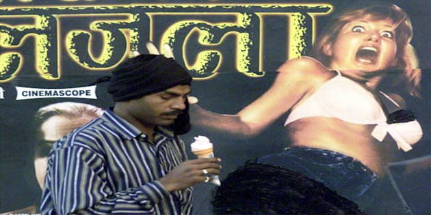 An Indian man passes a wall of a cinema displaying a poster of an adult movie in New Delhi.