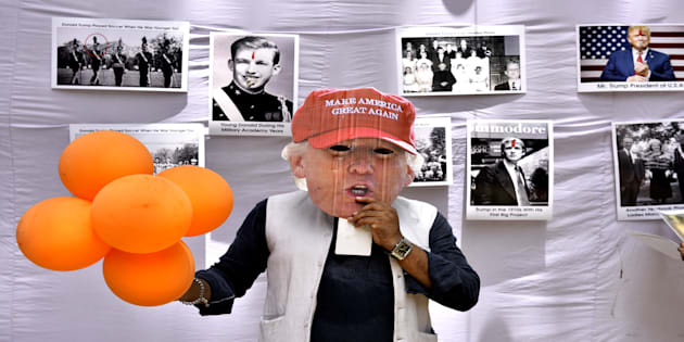 Member of Hindu Sena puts mask of US President Donald Trump as they celebrate his birthday on June 14, 2017 in New Delhi.