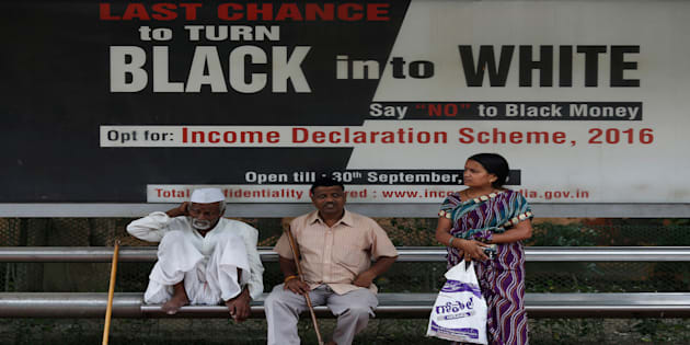 Passengers wait in front of an income tax billboard at a bus stop in New Delhi.