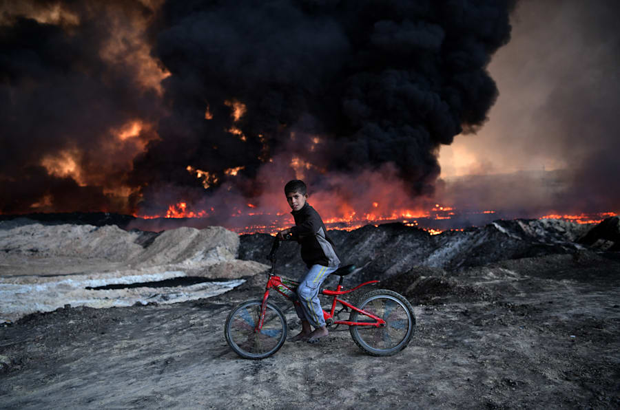 A boy pauses on his bike as he passes an oil field  set alight by retreating ISIS fighters ahead of the Mosul offensive, on October 21, 2016 in Qayyarah, Iraq.