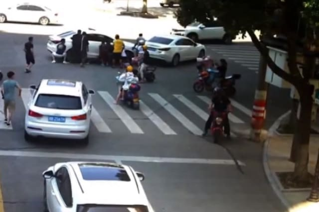 Passersby lift car up together to free biker trapped under the vehicle in China