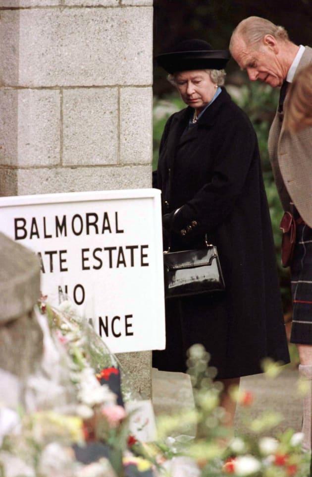 スコットランド・バルモラル城の門前で、故ダイアナ元英皇太子妃にささげられた花束や弔辞に見入るエリザベス女王とフィリップ殿下(1997年9月4日)