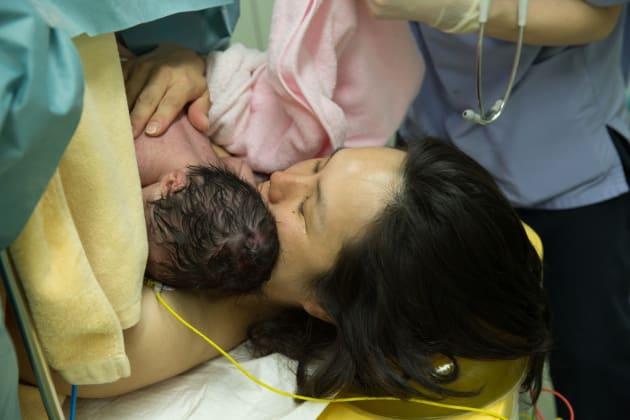 緊急帝王切開後、赤ちゃんを抱きしめて涙する母。